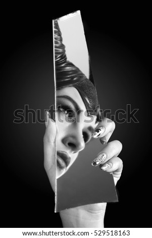 Beautiful girl with make-up and manicure looking away in a broken mirror. Portrait of beautiful woman with a shards of mirror. Well-groomed nails nail nail art design. Nail art manicure. Beauty hands.