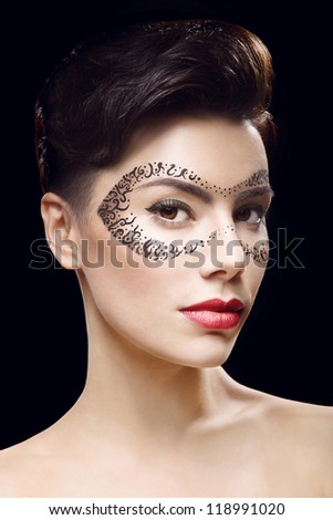 Beautiful girl with make up and mask on the black background