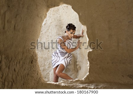 beautiful girl with makeup and tattoo near the cliffs and caves - stock photo