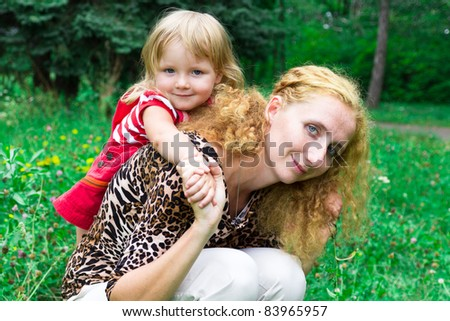 Beautiful girl with mother in the meadow outdoor - stock photo