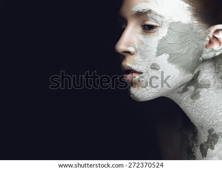 Beautiful girl with mud on his face. Cosmetic mask. Beauty face. Picture taken in the studio on a black background. - stock photo