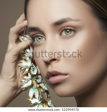 Beautiful girl with natural makeup and white nails and necklace with leaves. Fashion woman Portrait. Toned