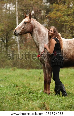 Beautiful girl with nice dress standing next to nice horse in autumn