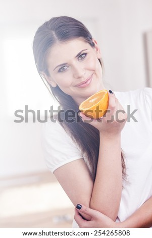 Beautiful girl with orange in a white room