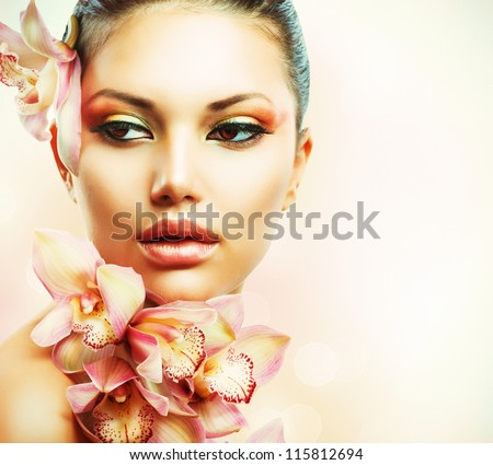 Beautiful Girl With Orchid Flowers.Beauty Woman Face.Vogue Styled Fashion Portrait. Professional Make-up.Makeup - stock photo