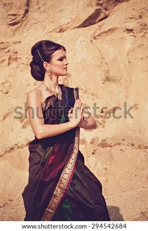 Beautiful girl with oriental make-up, Indian sari and Indian jewelry - stock photo