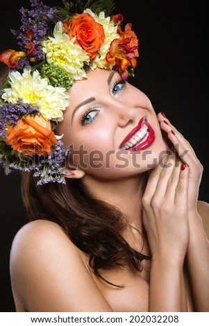 Beautiful girl with perfect skin and bright floral wreath on her head. Picture taken in the studio on a black background