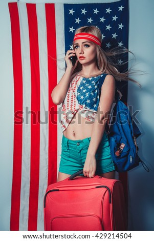 Beautiful girl with phone and bags in front of a flag of the USA - stock photo
