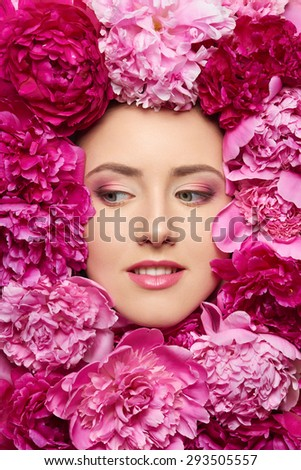 Beautiful girl with pink peony flowers. Closeup of beauty model woman face with perfect skin and professional makeup looking to the side