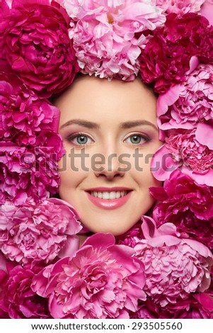 Beautiful girl with pink peony flowers. Closeup of beauty model woman face with perfect skin and professional makeup looking smiling at the camera - stock photo