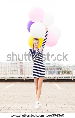 beautiful girl with ponytail hair in short black and white striped dress and white high sneakers walks forward holding bunch of multicolored balloons - stock photo