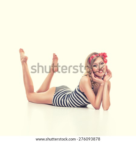 beautiful girl with pretty smile in pinup style on yellow background - stock photo