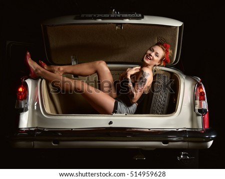 Beautiful girl with pretty smile laughing in pinup style and tattoo on hand in old vintage retro car open trunk