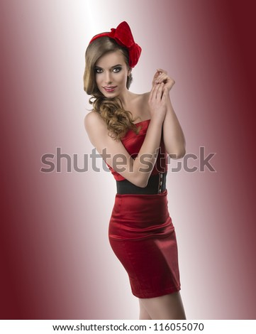 beautiful girl with red and elegant dress and one bow in the hair, she looks in to the lens with joined hands near the left shoulder - stock photo