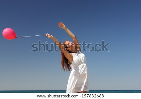 Beautiful girl with red balloon at blue sky background