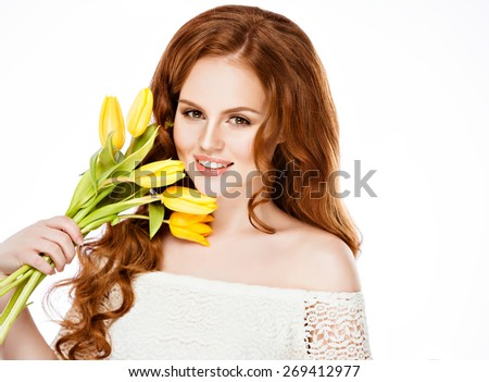 Beautiful girl with red hair in a braid, holds yellow tulips on white background in Studio