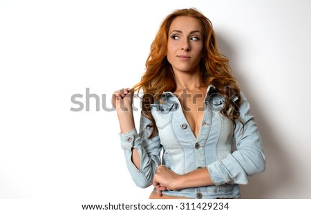 beautiful girl with red hair looks thoughtfully holding himself for a lock of hair. shot in studio - stock photo