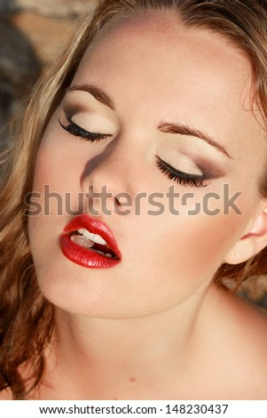 Beautiful girl with red lips with a piece of ice