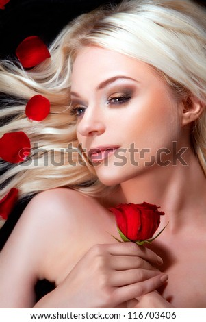 Beautiful girl with red roses in her blond hair. roses