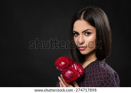 Beautiful girl with red roses in the studio - stock photo