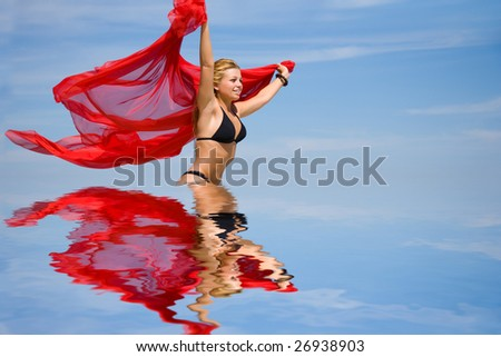 Beautiful girl with red sawl on beach