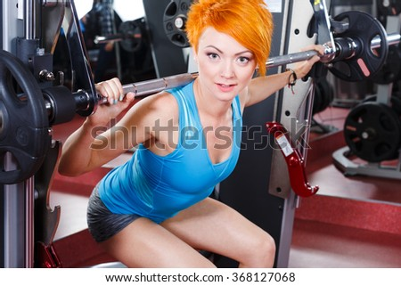 Beautiful girl with red short hair, big eyes and pink lips wearing gray shorts and blue shirt in gym, holding barbell and doing squatting, smiling.