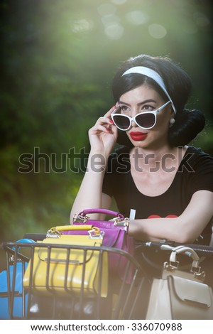 Beautiful girl with retro look wearing a black outfit having fun in park with bicycle. Outdoor lifestyle concept. Vintage scenery. Fashionable brunette with bike and basket with colored purses - stock photo