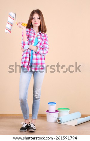 Beautiful girl with roller and paints in room - stock photo