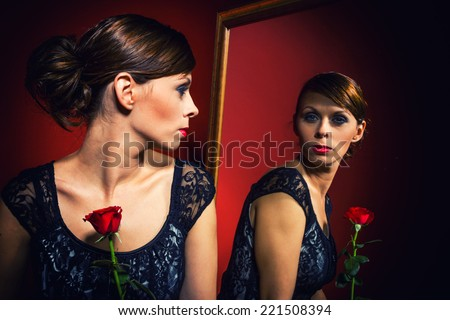 Beautiful Girl With rose looking at herself in the mirror - stock photo