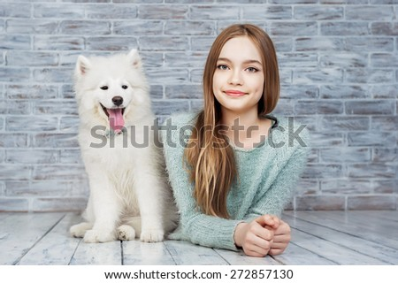 Beautiful girl with Samoyed dog - stock photo