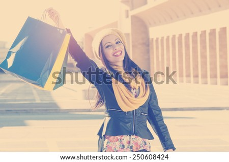 beautiful girl with shopping bag rejoices happy for purchases applied filter instagram style and a flare effect - stock photo
