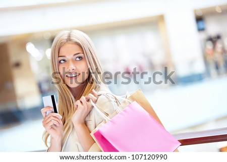 Beautiful girl with shopping bags and credit card - stock photo