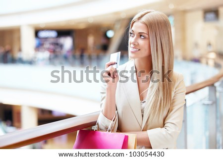 Beautiful girl with shopping bags and credit card at the store - stock photo