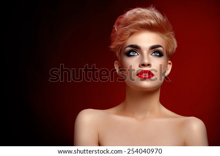 beautiful girl with short hair and makeup on red background - stock photo