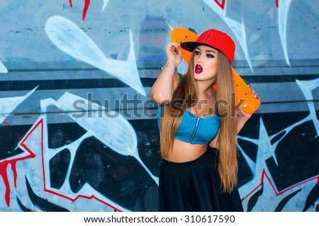 Beautiful girl with skateboard posing against graffiti wall. Attractive caucasian skater woman  - stock photo