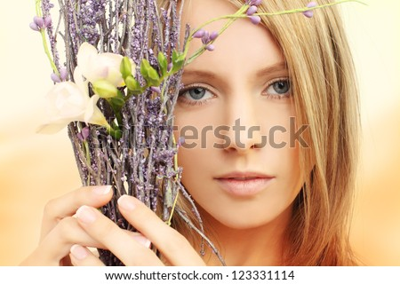 Beautiful girl with spring flowers - face closeup, portrait - stock photo