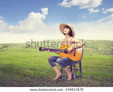 beautiful girl with straw hat plays guitar in the countryside - stock photo