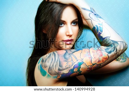 Beautiful girl with stylish make-up and tattooed arms. tattoo - stock photo