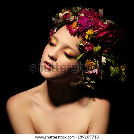 beautiful girl with stylish makeup and colorful flowers around her head