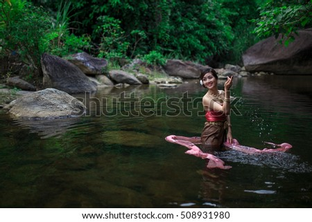Beautiful girl with Thai dressing was playing water in the river.