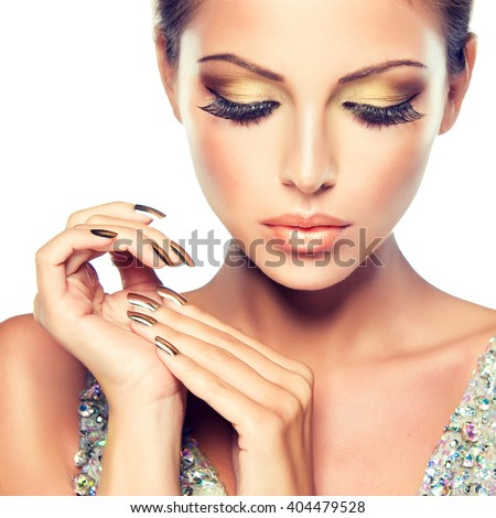 Beautiful girl with the Golden makeup and gold  metal nails.  Fashion woman Portrait - stock photo