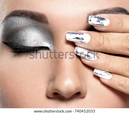 Beautiful girl with the silver makeup and  metal nails. Fashion woman portrait.