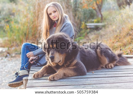 Beautiful girl with tibetan mastiff on the nature