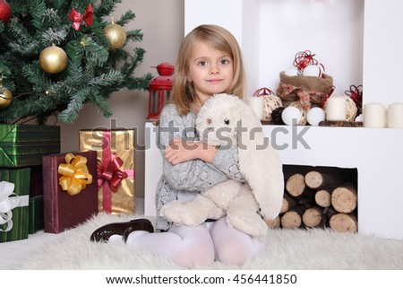 Beautiful girl with toy near a Christmas tree with gifts. New Year, happy child. - stock photo