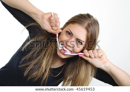 Beautiful girl with two toothbrushes on a white background.