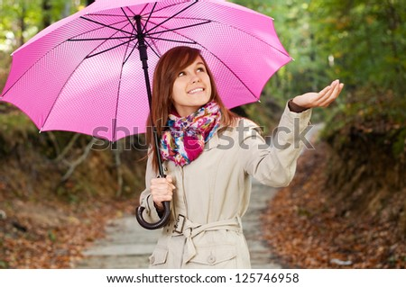Beautiful girl with umbrella checking for rain