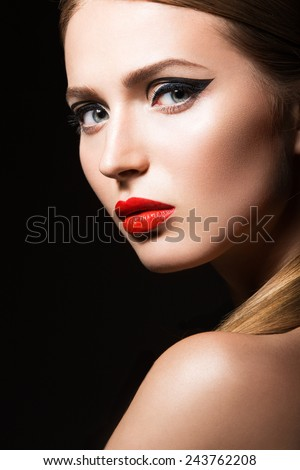 Beautiful girl with unusual black arrows on eyes and red lips. Beauty face. Picture taken in the studio on a black background. - stock photo