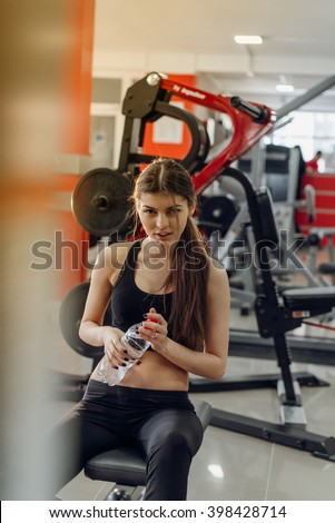 Beautiful girl with water at the gym