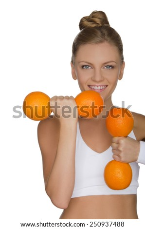 Beautiful girl with weights of ripe oranges isolated on white - stock photo