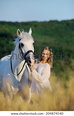 Beautiful girl with white horse in wheat field - stock photo